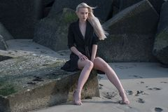 Blondes Mädchen im schwarzen Mantel auf Steinen Stockfoto