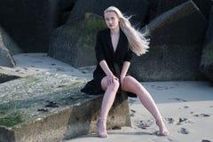 Blondes Mädchen im schwarzen Mantel auf Steinen Stockbild