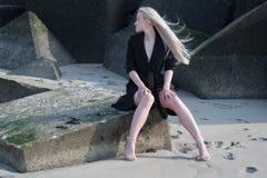 Blondes Mädchen im schwarzen Mantel auf Steinen Lizenzfreies Stockfoto