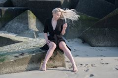 Blondes Mädchen im schwarzen Mantel auf Steinen Stockfotografie