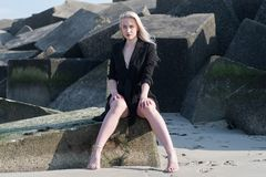 Blondes Mädchen im schwarzen Mantel auf Steinen Stockfotos