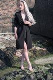 Blondes Mädchen im schwarzen Mantel auf Steinen Stockbilder