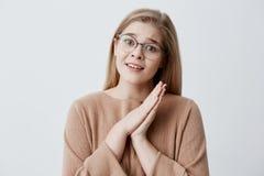 Blondes Mädchen im stilvollen Eyewear, der Palmen, gekleidet wurde zufällig, halten bedrängte zusammen vor ihr und hatte bedauern Lizenzfreie Stockfotografie