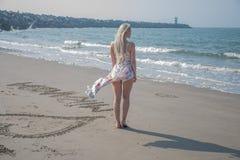 blondes Mädchen im Strandkleid und -wind Stockfotografie