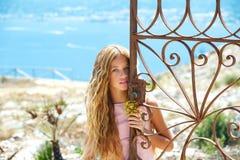 Blondes Mädchen im verrosteten Mittelmeertor in Meer Lizenzfreie Stockbilder