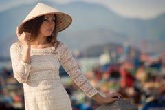 blondes Mädchen im Vietnamesekleid lehnt sich auf Damm Stockfotografie