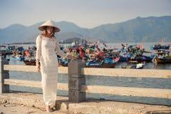 blondes Mädchen im Vietnamesekleid lehnt sich auf Damm Stockbild