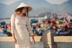 blondes Mädchen im Vietnamesekleid lehnt sich auf Damm Lizenzfreie Stockfotos