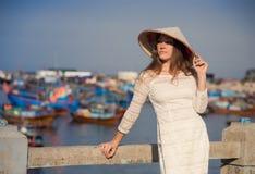 blondes Mädchen im Vietnamesekleid lehnt sich auf Damm Stockfotos