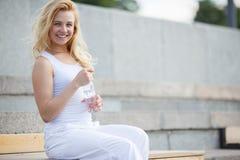 Blondes Mädchen im weißen Kleid, das auf Bank und dem Stillstehen sitzt Stockbild
