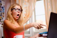 Blondes Mädchen ist überrascht zeigend und Finger auf Laptopschirm Lizenzfreies Stockbild