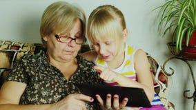 Blondes Mädchen 6 Jahre mit ihrer Großmutter, die eine Tablette verwendet stock video