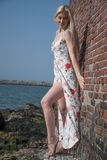 blondes Mädchen kleidete auf dem Strand nahe der Wand und den Steinen an Stockbild
