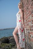 blondes Mädchen kleidete auf dem Strand nahe der Wand und den Steinen an Lizenzfreies Stockfoto