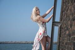 Blondes Mädchen kleidete in einem Strand auf der Leiter an Stockfoto