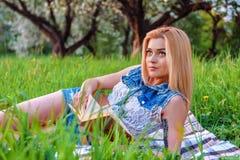 Blondes Mädchen las Buch im Park Stockfotografie