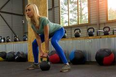 Blondes Mädchen macht die heftigen Verlangen, die ein Gewicht mit einem grünen handl halten stockbild