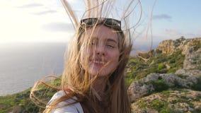 Blondes Mädchen macht selfie auf dem Hintergrund der überraschenden Natur, Felsen, Meer, Grün Langhaariges jugendlich Mädchen läc stock video footage