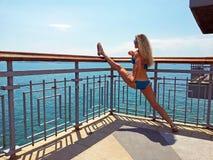 Blondes Mädchen macht Spalte auf dem balcon Lizenzfreie Stockbilder