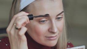 Blondes Mädchen malt ihre Augenbrauen stock footage