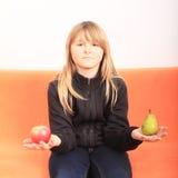 Blondes Mädchen mit Apfel und Birne Stockbilder