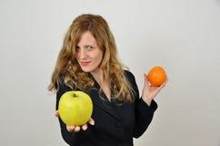 Blondes Mädchen mit Apfel und Orange kleidete im Büroanzug an Lizenzfreies Stockfoto