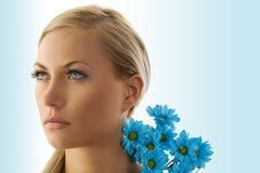 Blondes Mädchen mit blauem Gänseblümchen lizenzfreie stockbilder