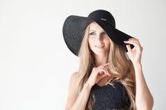 Blondes Mädchen mit blauen Augen ein Hut mit einem Rand auf einem weißen Hintergrund Lizenzfreie Stockfotos