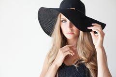 Blondes Mädchen mit blauen Augen ein Hut mit einem Rand auf einem weißen Hintergrund Lizenzfreies Stockbild