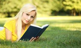 Blondes Mädchen mit Buch auf grünem Gras Schöner Wo Stockfotografie