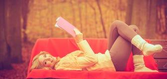 Blondes Mädchen mit Buch im Herbstpark Lizenzfreies Stockfoto