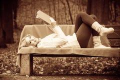Blondes Mädchen mit Buch im Herbstpark Lizenzfreie Stockfotos