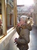 Blondes Mädchen mit dem blonden Haar malt ihre Lippen mit Lippenstift nahe dem Fenster lizenzfreie stockbilder