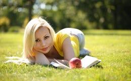 Blondes Mädchen mit dem Buch und Apple, die auf grünem Gras liegen Stockfoto
