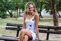 Blondes Mädchen mit dem gelockten Haar, das auf der Bank in einem Park, Blick sitzt Lizenzfreies Stockfoto