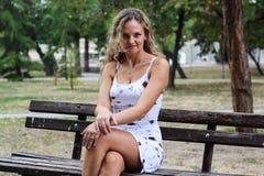 Blondes Mädchen mit dem gelockten Haar, das auf der Bank in einem Park mit sitzt Stockfotografie