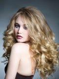 Blondes Mädchen mit dem gesunden gewellten Haar Lizenzfreie Stockfotos