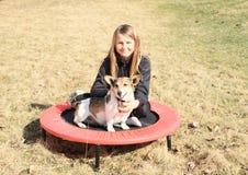 Blondes Mädchen mit dem Hund, der auf Trampoline sitzt Lizenzfreie Stockbilder