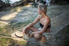 Blondes Mädchen mit dem Hut, der auf einem Aufenthaltsraum am Strand im Sommer sitzt lizenzfreie stockfotos