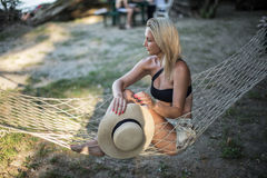 Blondes Mädchen mit dem Hut, der auf einem Aufenthaltsraum am Strand im Sommer sitzt stockfotografie