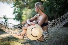 Blondes Mädchen mit dem Hut, der auf einem Aufenthaltsraum am Strand im Sommer sitzt lizenzfreies stockbild