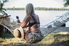 Blondes Mädchen mit dem Hut, der auf einem Aufenthaltsraum am Strand im Sommer sitzt stockfotos