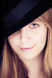 Blondes Mädchen mit dem Hut, der Kamera betrachtet Stockbild