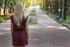 Blondes Mädchen mit dem langen Haar in Burgunder-Kleid, das im Park steht Stockbild
