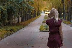 Blondes Mädchen mit dem langen Haar in Burgunder-Kleid, das im Park steht Stockfoto