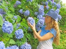 Blondes Mädchen mit dem langen Haar lächelnd, die Blumen betrachtend, die herein halten Lizenzfreie Stockfotos