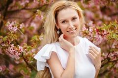 Blondes Mädchen mit dem langen Haar lächelt vor dem hintergrund des Rosas Stockbild