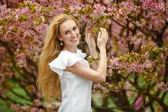 Blondes Mädchen mit dem langen Haar lächelt vor dem hintergrund des Rosas Stockfotos