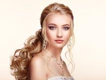 Blondes Mädchen mit dem langen und glänzenden gelockten Haar Lizenzfreie Stockfotografie