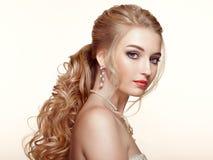 Blondes Mädchen mit dem langen und glänzenden gelockten Haar Stockbilder